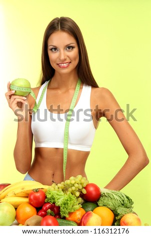 beautiful young woman with fruits and vegetables, on green background