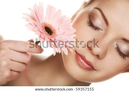 Beautiful young woman with gerber flower isolated on white background - stock photo