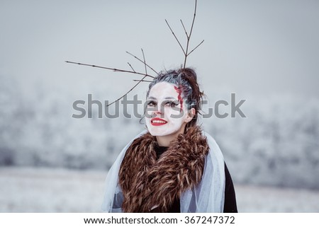 Beautiful young woman with ghost makeup mask and old-fashioned dress in front of white forest in the winter. Face painted as a traditional day of the dead. Color toned image. - stock photo