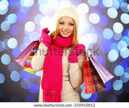 Beautiful young woman with gift bags on bright background - stock photo