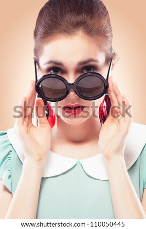 Beautiful young woman with glamour red lips wearing round plastic-rimmed sunglasses and fancy plastic earrings, she's surprised and looking over the top of her glasses. Colored background, pinup style