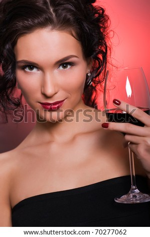 Beautiful young woman with glass of red wine - stock photo