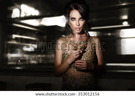 Beautiful young woman with glass of  wine standing  in interior. - stock photo