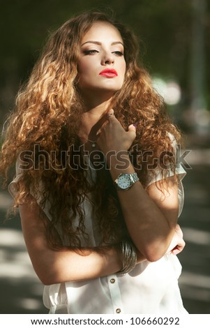 Beautiful young woman with gorgeous curly fair outdoors - stock photo