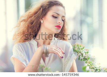 Beautiful young woman with gorgeous curly hair outdoors  - stock photo