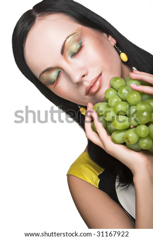 Beautiful young woman with green grape