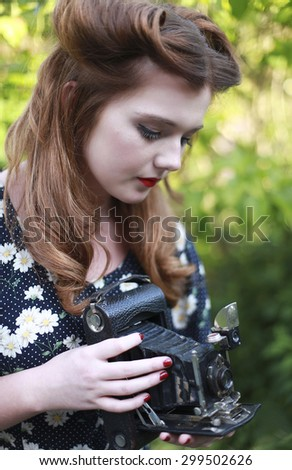 Beautiful young woman with hair in victory rolls  from the forties era holding a camera - stock photo