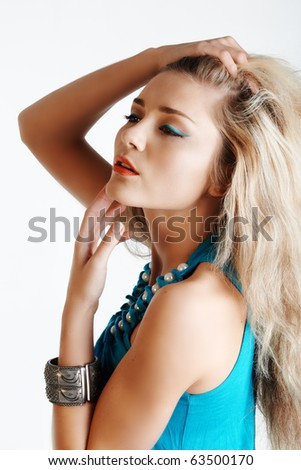 beautiful young woman with hand in long hair wearing bright blue eyeliner and a matching dress with pearls. - stock photo