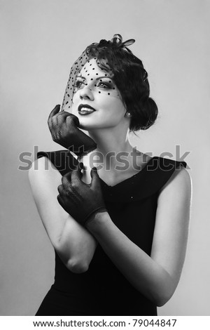Beautiful young woman with hands on chin retro style portrait - stock photo
