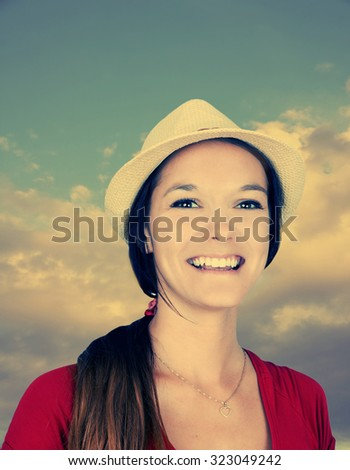 Beautiful young woman with hat and cloudy sky, filter effect - stock photo