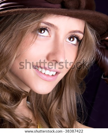 Beautiful young woman with hat is smiling, studio shot