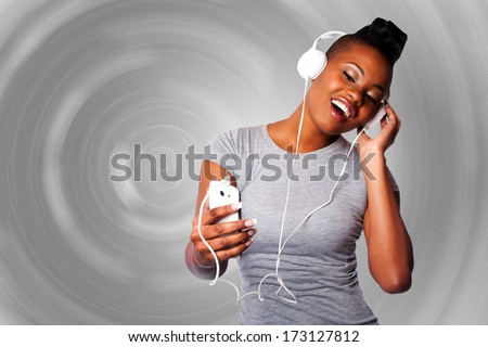Beautiful young woman with headphones and mobile device listening grooving singing to music, gray circular background. - stock photo