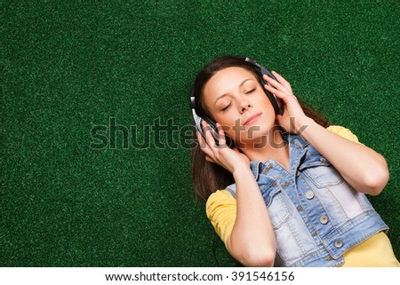 Beautiful young woman with headphones enjoys in music while lying down on grass.Enjoy music - stock photo