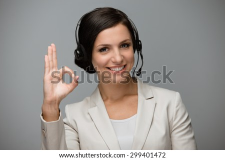 Beautiful young woman with headphones looking at camera at call center and showing ok sign. Grey background - stock photo