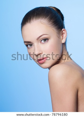 Beautiful young woman with heathy clean skin - blue background - stock photo