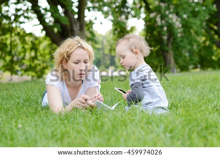 Beautiful young woman with her baby in the park.