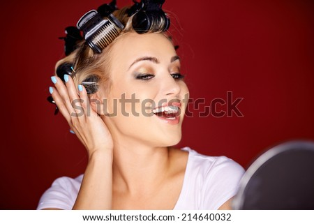 Beautiful young woman with her blond hair in curlers primping in front of a mirror laughing and flirting with herself in a narcissistic way - stock photo