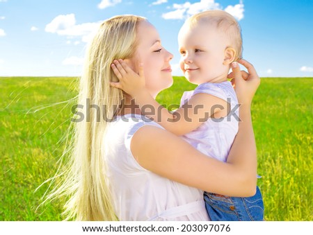 beautiful young woman with her daughter outdoor on a summer day - stock photo