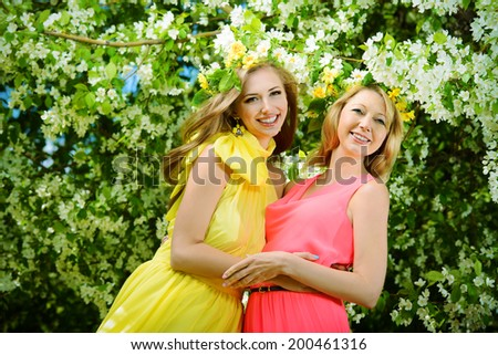 Beautiful young woman with her mother in the spring garden among apple blossom.  - stock photo