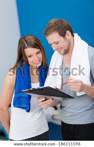 Beautiful young woman with her personal trainer at the gym smiling as they discuss her performance on a clipboard held by the man - stock photo