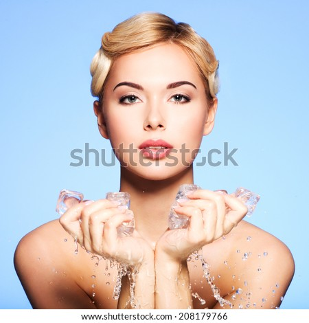 Beautiful young woman with ice in her hands on a blue background.