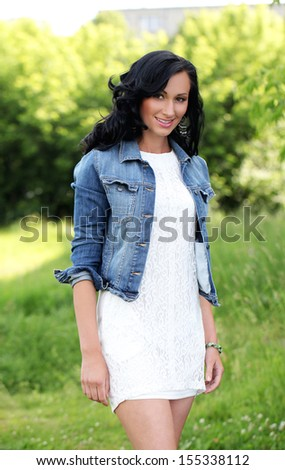 Beautiful young woman with jeans jacket in a park