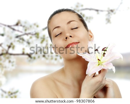 Beautiful young woman with lily flower IN NATURE