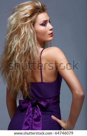 beautiful young woman with long blond hair wearing a purple evening dress. - stock photo