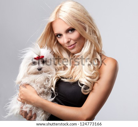 Beautiful Young Woman with Long Blonde Hair holding small dog - stock photo
