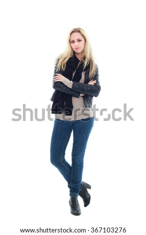 beautiful young woman with long blonde hair wearing black leather jacket and blue jeans.  standing pose with arms crossed, isolated on white background. - stock photo