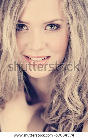beautiful young woman with long curly blond hair and natural make-up smiling happily with cross process effect from 16 Bit RAW - stock photo