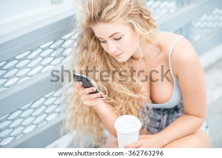 Beautiful young woman with long curly hair and a takeaway coffee cup, chatting and surfing on the phone against urban metal railing background. - stock photo