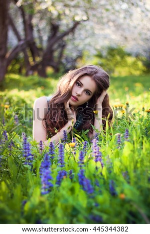 Beautiful young woman with long curly hair sitting in the blooming garden, long blue dress.