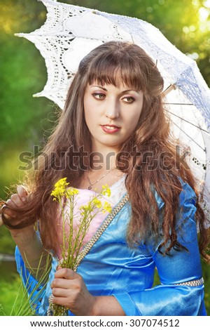 Beautiful young woman with long hair and umbrella on summer meadow - stock photo