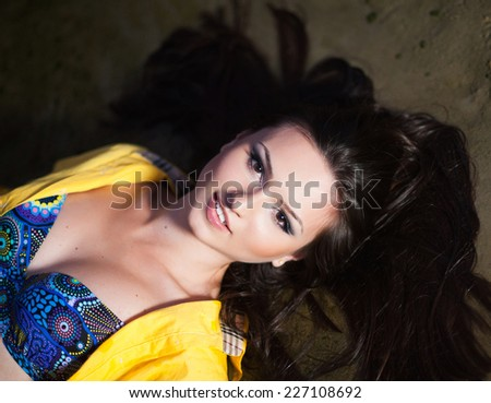 Beautiful young woman with long hair laying on river sand in swimsuit and yellow shirt and smiling