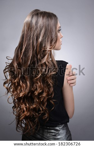 Beautiful young woman with long hair on grey background - stock photo