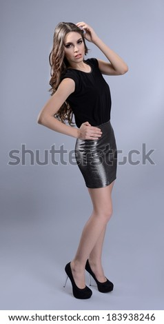 Beautiful young woman with long hair on grey background