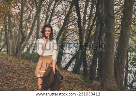 Beautiful young woman with long hair posing in a city park