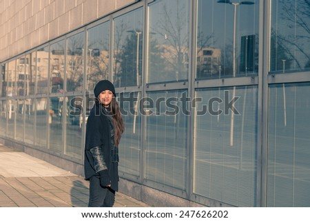 Beautiful young woman with long hair posing in the city streets