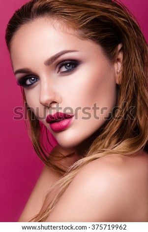 Beautiful young woman with long hair posing on pink shiny background. Healthy skin and long smooth hair. Pink lips - stock photo