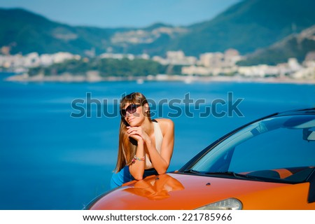 Beautiful young woman with long hair standing near orange cabriolet at the Mediterranean sea coast  - stock photo