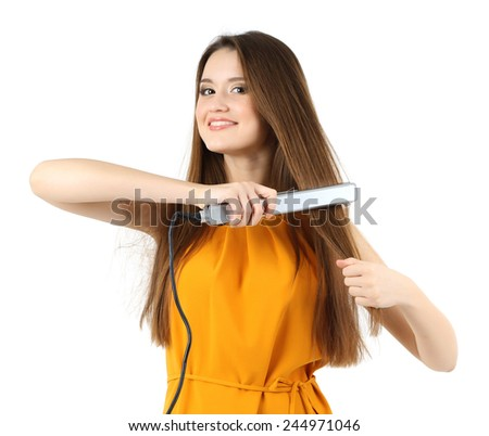 Beautiful young woman with long hair using hair straighteners isolated on white - stock photo