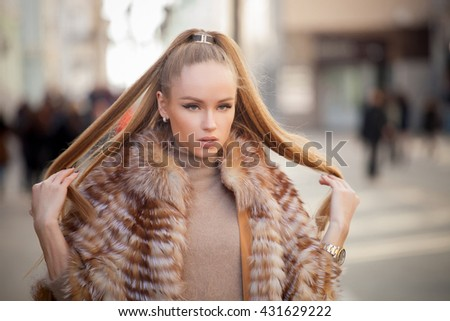 Beautiful young woman with long hair walking in the city