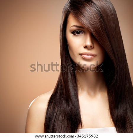 Beautiful young woman with long straight brown hair. Fashion model posing at studio over beige background - stock photo