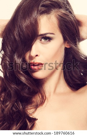 beautiful young woman with long wavy brown hair studio shot - stock photo