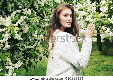 Beautiful young woman with long wavy hair thin slender figure perfect body and pretty face natural make-up wearing a knitted grey cardigan in blooming garden. Stylish spring bohemian outfits.  - stock photo
