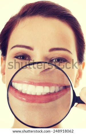 Beautiful young woman with magnifying glass on mouth. - stock photo