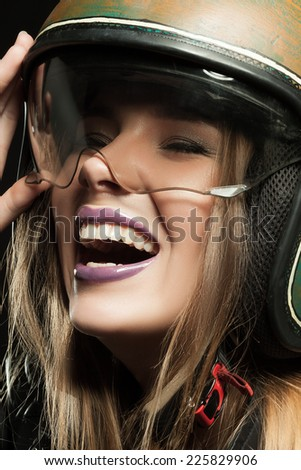 Beautiful young woman with make-up in a motorcycle helmet on a black background close up - stock photo