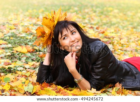 Beautiful young woman with maple leaves in a autumn park