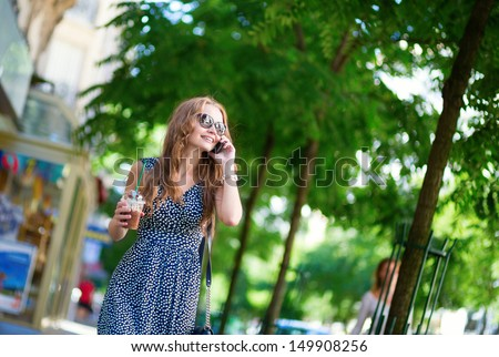 Beautiful young woman with mobile phone in the street - stock photo